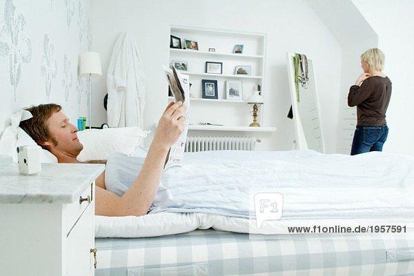 Mann bleibt im Bett und liest Zeitung