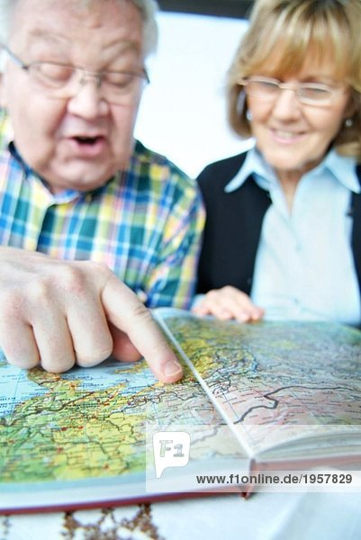 Mann zeigt in einen Atlas