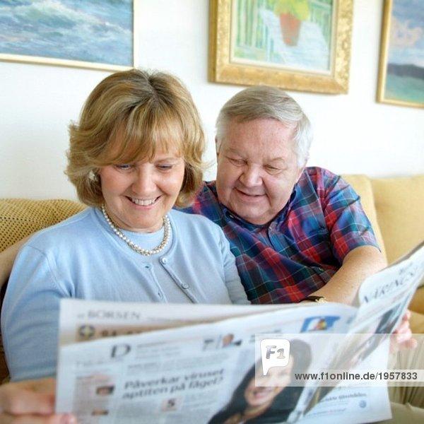 Ein Paar liest die Zeitung in der Couch.