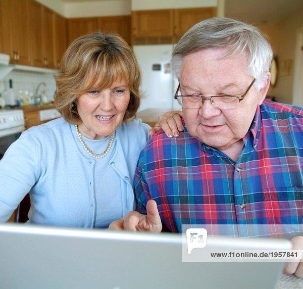 Paar sitzend mit Computer