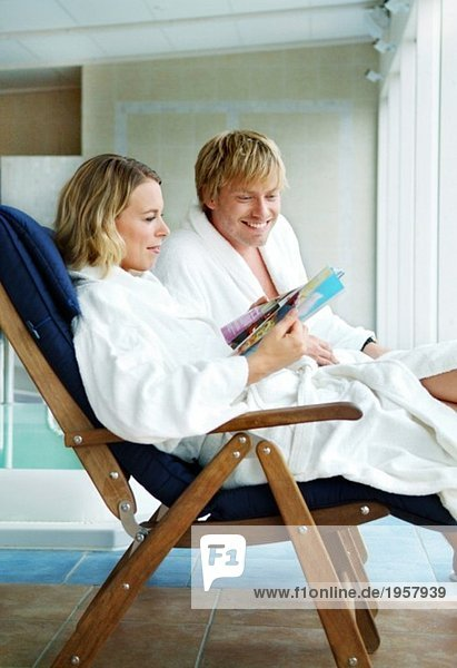 Junges Paar beim Stöbern im Spa-Magazin