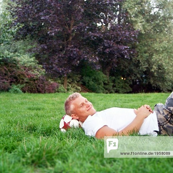 Guy lying in a park and resting after playing football