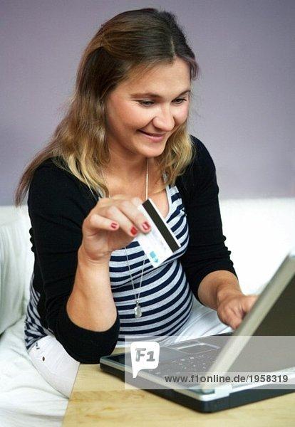 Junge Frau mit Computer und Kreditkarte