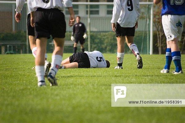Spieler auf einem Fußballfeld liegend