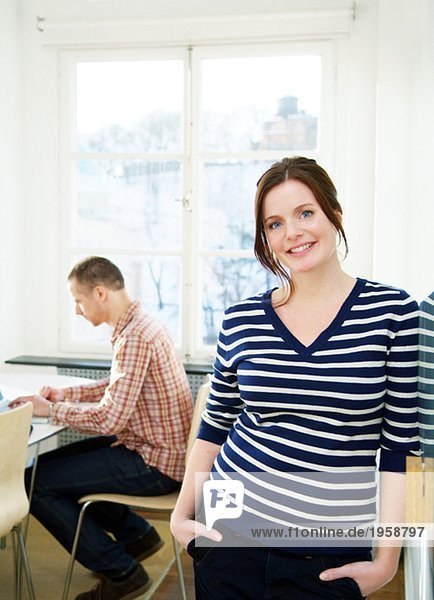 Young woman together with a colleague at an office