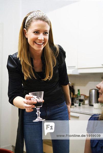 Frau gibt ein Glas Wein.