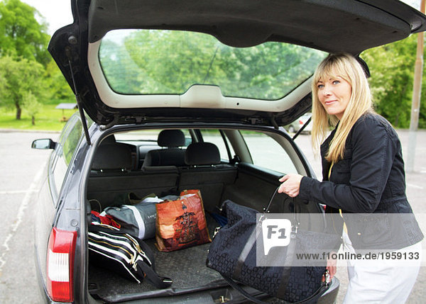 Frau  die ihr Auto packt