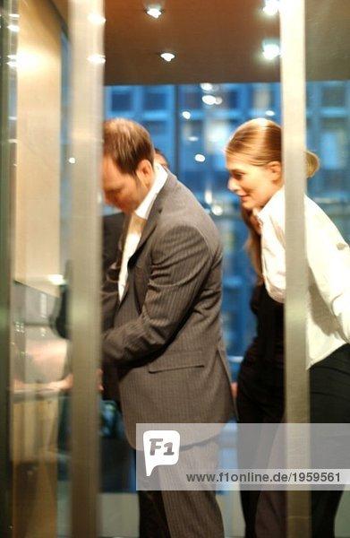 Mann und Frau hinter Aufzugstüren