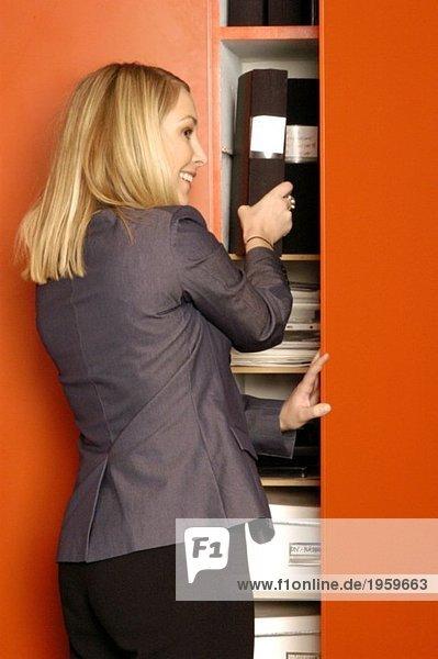 Frau nimmt Ordner aus dem Schließfach