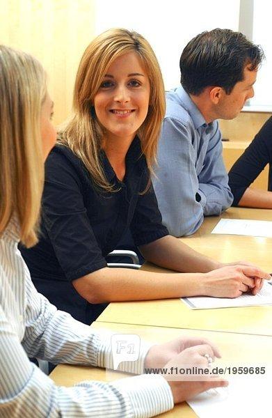 Glückliche Frau in der Mitte des Konferenztisches