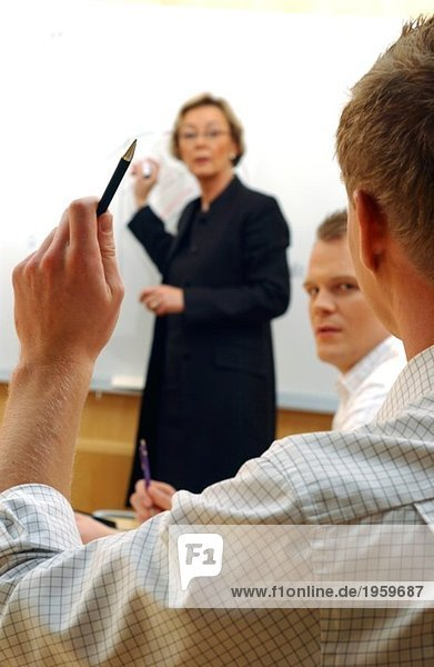 Mann hebt die Hand im Konferenzraum