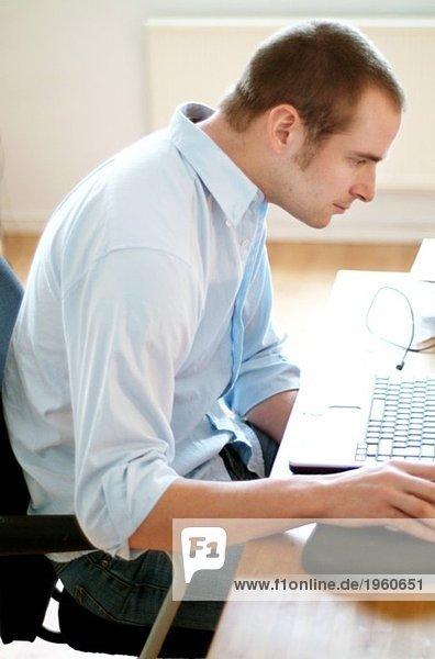 Junger Mann im Büro vor dem Computer