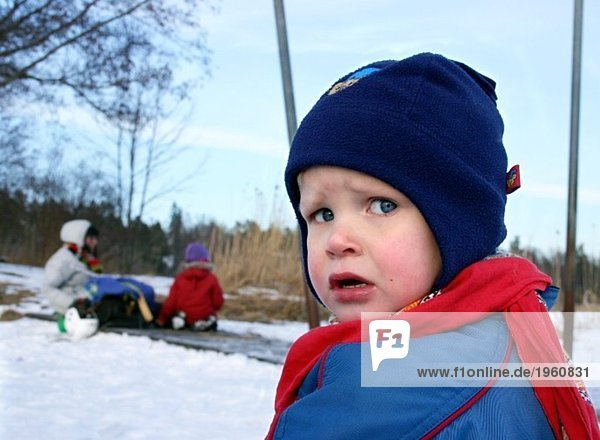 Upset boy in winter clothes