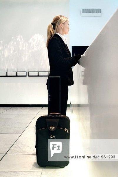 Frau beim Einchecken in ein Hotel