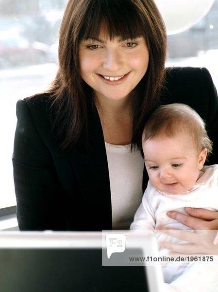 Junge Frau mit Kind und Computer
