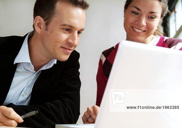 Junger Mann und Frau schauen auf den Bildschirm