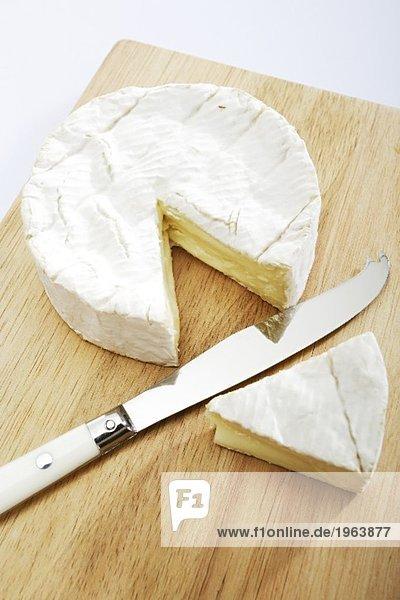 Angeschnittener Camembert auf einem Holzbrett mit Messer