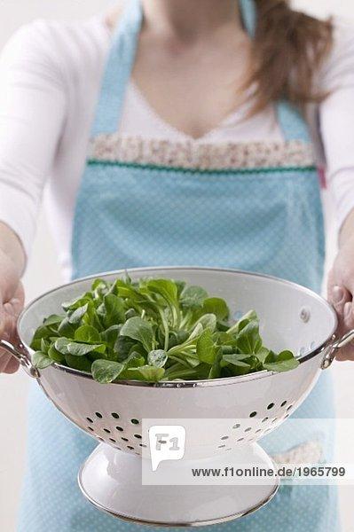 Frau hält Seiher mit Feldsalat