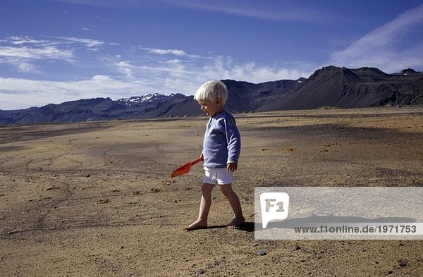 A little boy with a plastic spade in the sand at Snaefellsnes  Iceland