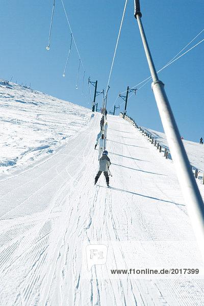 Young skiers using ski lift on ski slope  low angle view