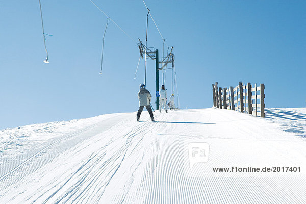 Young skiers going up hill on ski lift  rear view
