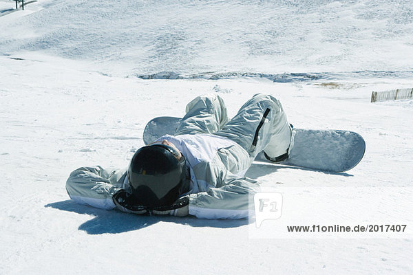 Young snowboarder lying on back in snow  hands behind head  full length