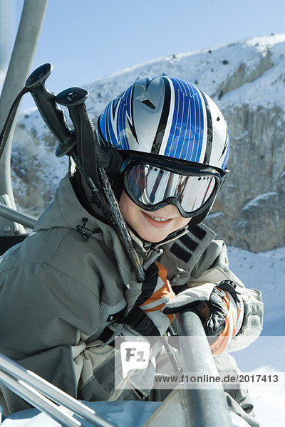 Young skier in chair lift  dressed in ski goggles and helmet  smiling at camera  portrait