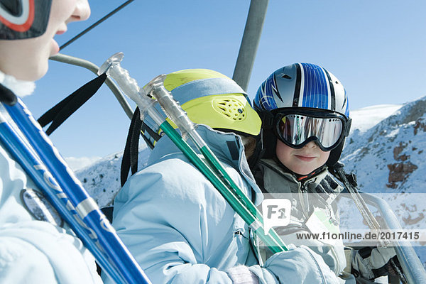 Young skiers on chair lift  one whispering in the other's ear
