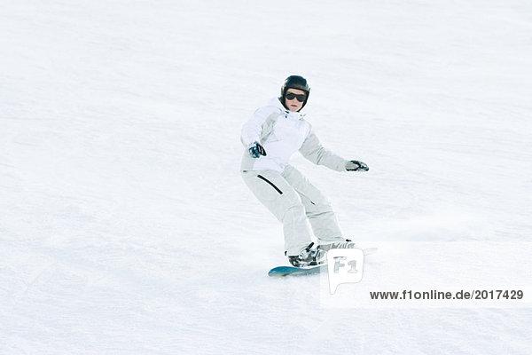 Teenage girl snowboarding on ski slope  full length