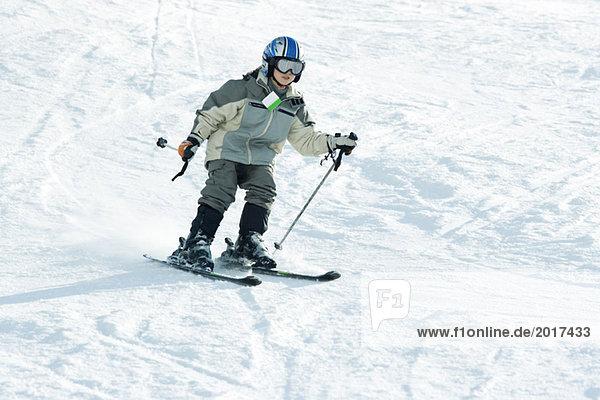 Boy skiing down ski slope  full length
