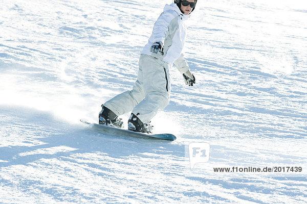 Teenage girl snowboarding down ski slope  cropped view