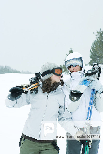 Two young friends carrying skis on shoulders  looking at each other