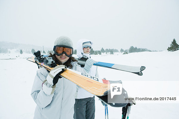 Two young skiers walking together  carrying skis on shoulders  one looking at camera