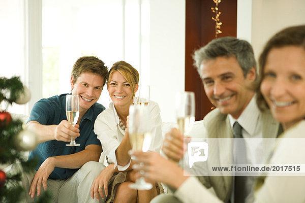 Erwachsene Freunde stoßen mit Champagner an und lächeln in die Kamera.