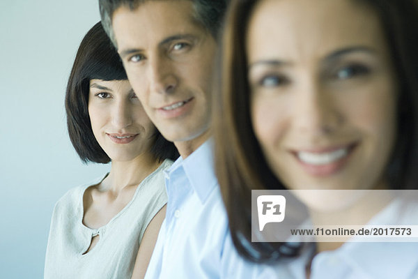 Business team in a row smiling at camera  head and shoulders  focus on woman in background  portrait