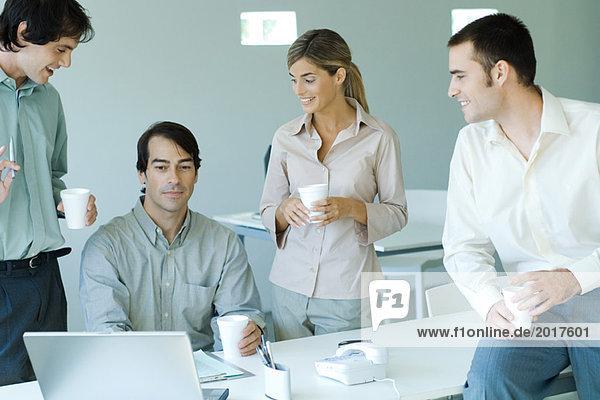 Geschäftsfreunde versammelten sich um einen männlichen Kollegen  der am Laptop saß und Einwegbecher hielt.