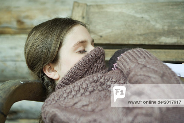 Teen girl lying down with turtleneck pulled up over face and mouth  eyes closed