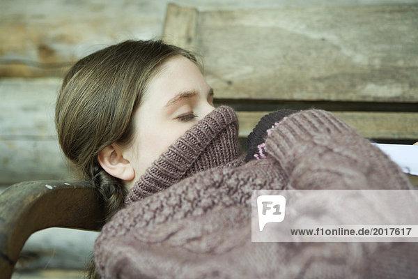 Teenagermädchen liegend mit Rollkragenpulli über Gesicht und Mund gezogen  Augen geschlossen