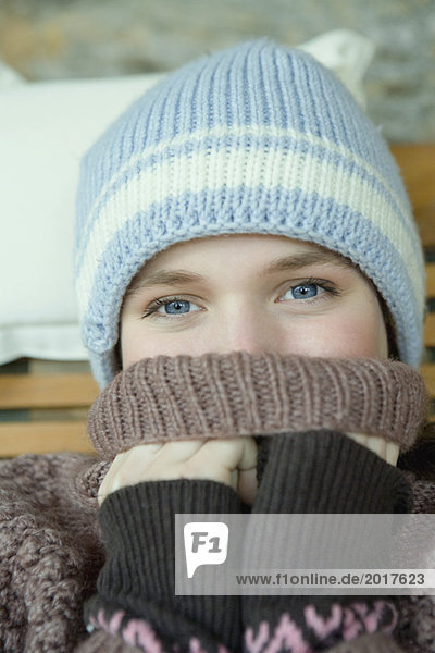 Teen girl covering mouth with turtle neck sweater  portrait