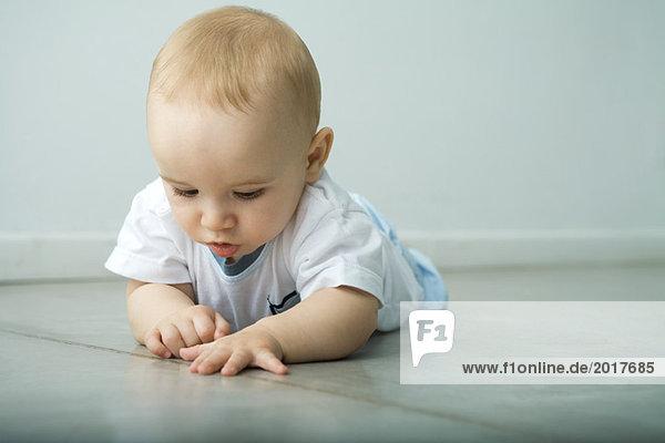 Baby auf dem Boden liegend  auf die Naht im Boden schauend