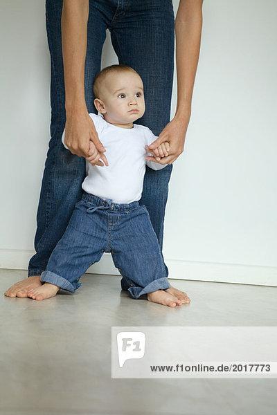 Baby steht zwischen den Beinen der Mutter und schaut weg.