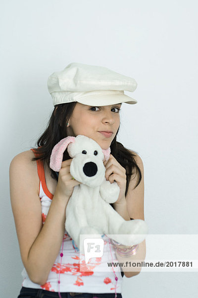 Teenage girl holding up stuffed toy  smiling at camera  portrait