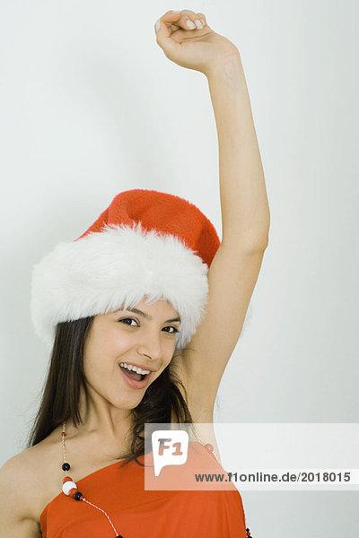 Junge Frau mit Nikolausmütze  lächelnd vor der Kamera  Arm erhoben  Portrait