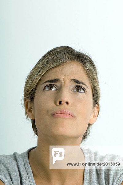 Frau furchende Stirn  nach oben schauend  Portrait