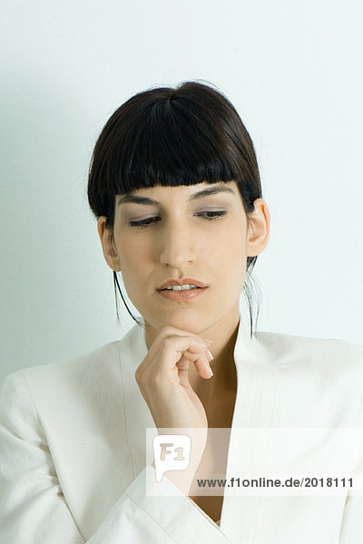 Young businesswoman  holding hand under chin  looking away  portrait
