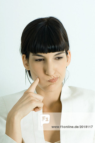 Junge Geschäftsfrau bläst Wangen aus  hält Finger an Wange  schaut weg  Porträt