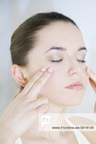 Frau berührt Wangen  Augen geschlossen  Kopf und Schultern