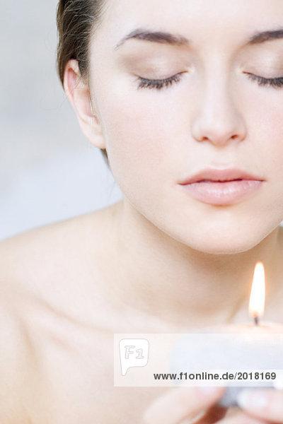 Junge Frau hält Kerze  Augen geschlossen  Ansicht abgeschnitten