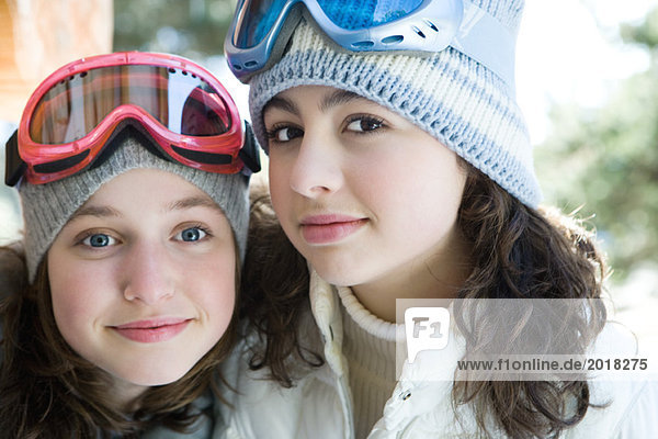 Two young friends wearing knit hats and ski goggles  smiling at camera  portrait