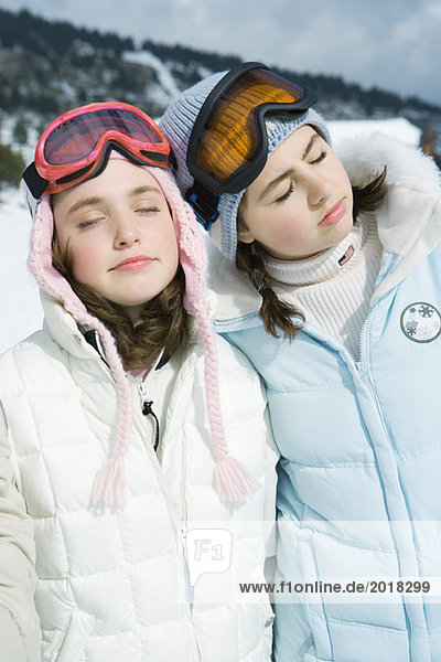 Two teenage girls standing side by side  eyes closed  dressed in winter clothing  portrait